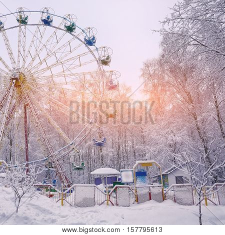 Snow covered Ferris wheel surrounded by snowcovered trees. Lots of snow