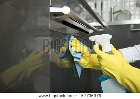 Close up of female hands in rubber protective yellow gloves cleaning the cooker oven panel with rag and spray bottle detergent. Home, housekeeping concept