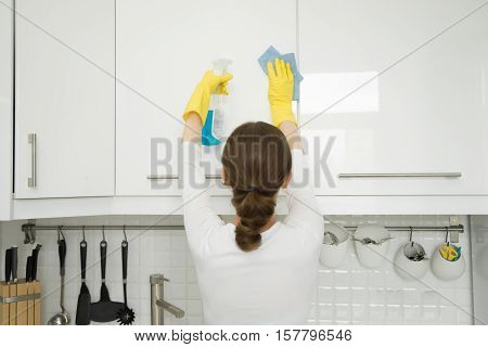 Rear view at an attractive young woman cleaning a surface of white kitchen wall cabinet, wearing rubber protective yellow gloves, with rag and spray bottle detergent. Home, housekeeping concept