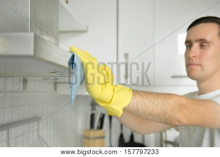 Closeup of male hands in rubber protective yellow gloves cleaning the kitchen metal extractor hood with rag. Home, housekeeping concept