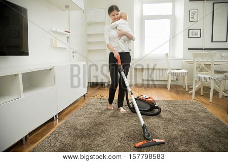 Happy smiling woman doing vacuum cleaning the carpet in the living room holding a child, modern interior. Busy mum. Home, housekeeping concept.