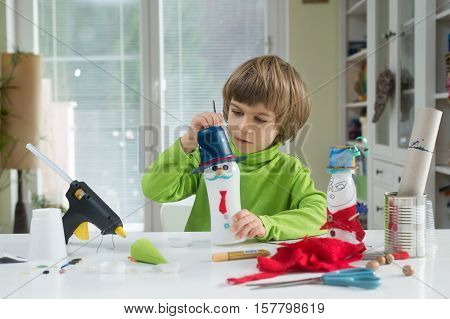 Little boy being creative making homemade do-it-yourself toys out of yogurt bottle and paper. Supporting creativity learning by doing hand craft. Helping child gain access to a creative way of seeing.