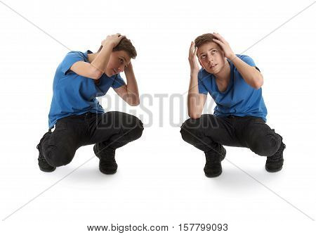 Cute teenager boy in blue T-shirt sitting and closing head with hands over white isolated background full body