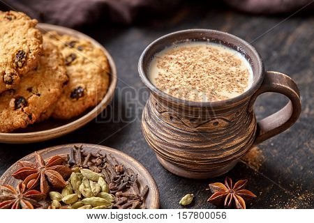 Masala pulled tea chai latte traditional hot Indian sweet milk spiced drink, ginger, fresh spices and herbs blend, anise organic infusion healthy wellness beverage teatime ceremony in rustic clay cup