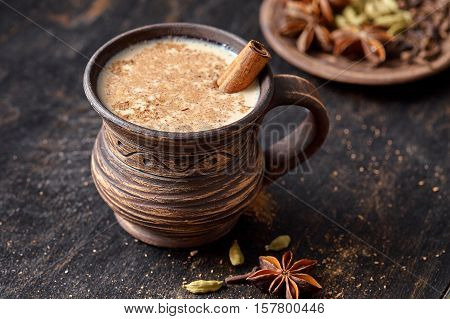 Masala pulled tea chai latte homemade hot Indian sweet milk spiced drink, ginger, fresh spices and herbs blend, anise organic infusion healthy wellness beverage teatime ceremony in rustic clay cup