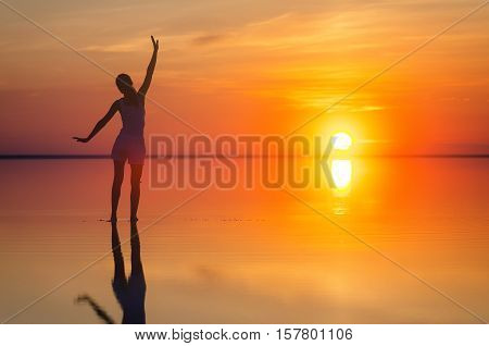 Beautiful female model open arms under the sunrise at seaside. Calm water of salt lake Elton reflects silhouette of woman. Sun goes under horizon. Girl stands alone in water. Sun reflects in Elton's water.