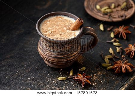 Masala pulled tea chai latte hot Indian sweet milk spiced drink, ginger, fresh spices and herbs blend, anise organic infusion healthy wellness beverage teatime ceremony in rustic clay cup