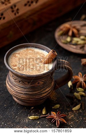 Masala pulled tea chai latte hot Indian sweet milk spiced drink, nutmeg, fresh spices and herbs blend, anise organic infusion healthy wellness beverage teatime ceremony in rustic clay cup