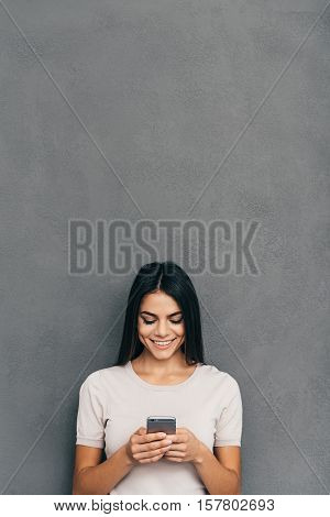 Texting to friend. Attractive young woman holding smart phone and looking at it with smile while standing against grey background with copy space upon her head
