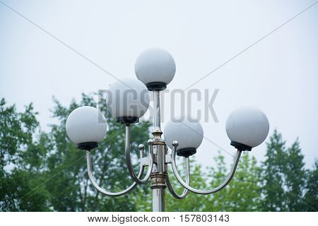 Top side of the lamp post with round plafonds. Green trees on background.