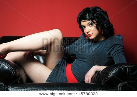 young woman relaxing on her couch over red background