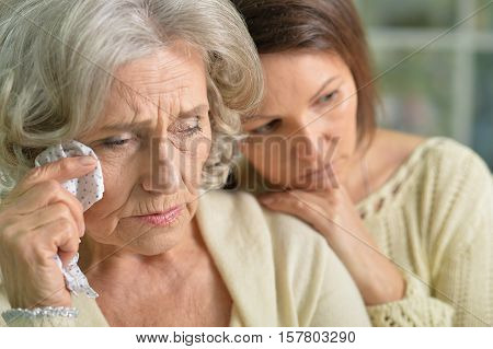 Portrait of sad senior and young women