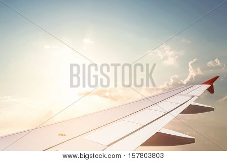 Wing of air plane transport flying in sky with sun. concept of air transportation background.