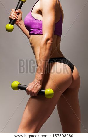 Body, back and buttock of the fit woman with dumbbells exercising on grey background