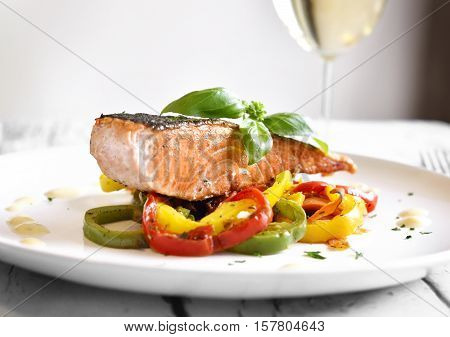 Delicious Salmon filet with decorative basil leaf and multicolored paprika or bell pepper vegetable. Healthy eating scene.