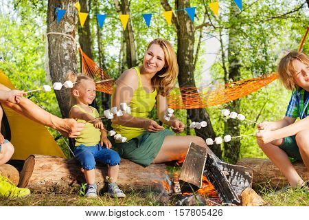 Portrait of happy young mother and kids roasting marshmallows on the sticks over the fire at campsite in summer