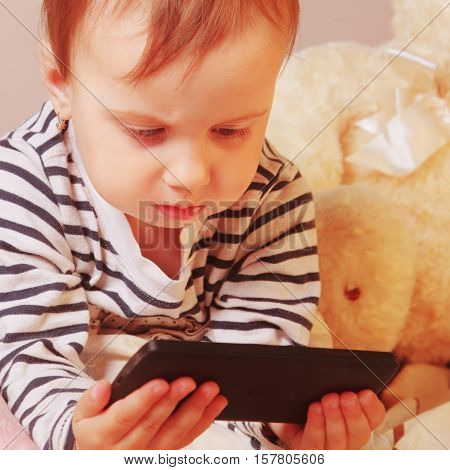 Social Media addiction. Little baby girl holding phone (psychological problems media mania education)