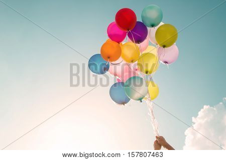 Hands of girl holding multicolored balloons done with a retro vintage filter effect concept of happy birthday in summer and wedding honeymoon party (Vintage color tone)