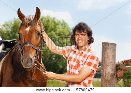 Happy young man holding his beautiful bay horse by a bridle next to the enclosure fence