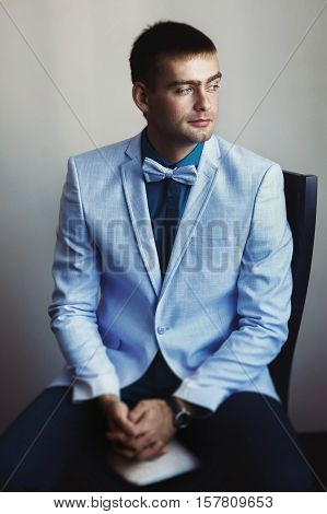 Young man in blue jacket with a white bow tie waits