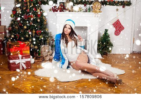 winter christmas people concept- Beautiful sexy brunette female lush breasts model snowflake dressed Santa Claus erotic lingerie white fur. over snow background