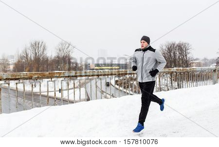 fitness, sport, people, music and healthy lifestyle concept - young man in earphones running along snow covered winter bridge
