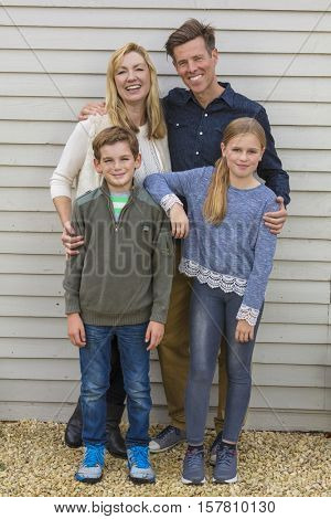 Portrait shot of an attractive, successful and happy family, man, woman, girl and boy child, mother, father, son and daughter outside