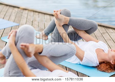yoga, fitness, sport, and healthy lifestyle concept - women making supine pigeon pose on mat outdoors on river or lake berth