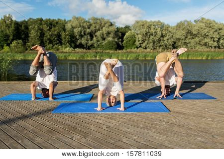 yoga, fitness, sport, and healthy lifestyle concept - group of people making tripod egg pose n mat outdoors on river or lake berth