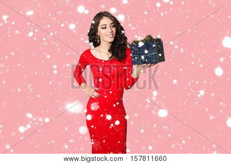 people luxury holidays and sale concept - picture of lovely woman in red dress with shopping bag. over snow background portrait