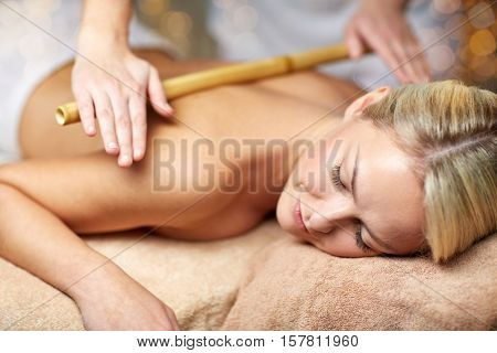 people, beauty, spa, healthy lifestyle and relaxation concept - close up of beautiful young woman lying with closed eyes and having bamboo massage in spa