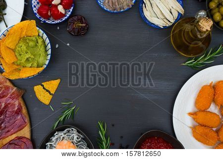 Table with spanish tapas - anchovies with peppers padron, jamon, croquetes, guacamole and olives, top view flat lay frame with copy space