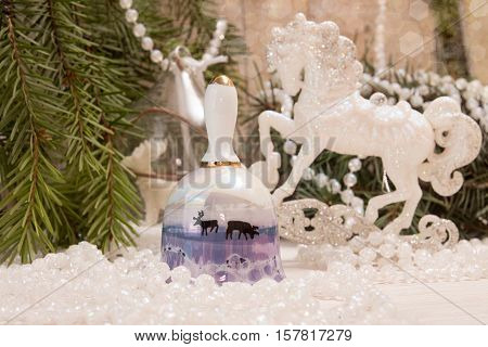 Christmas New Year holiday concept. Bell with deers white horse garland and fir tree branch on white background