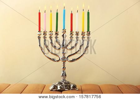 Menorah with colorful candles for Hanukkah on wooden surface against light background