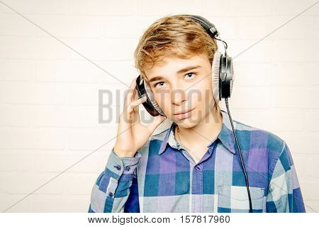 Modern teenage boy enjoys the music in headphones. Studio shot. Youth culture.