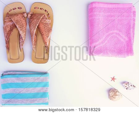 Sandals, towel and a striped tank top on a light background. Things for the beach and seashells, flat lay, top view