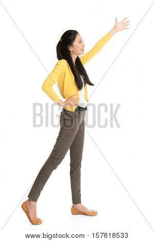 Full length Asian woman hand raised reaching or grabbing something, standing isolated on white background.