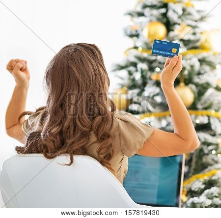 Young Woman With Credit Card And Laptop Rejoicing Success Near Christmas Tree