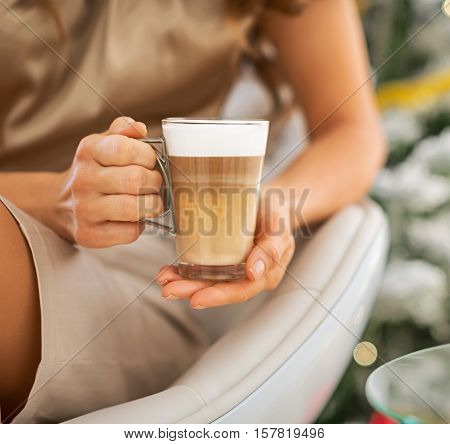 Closeup On Latte Macchiato In Hand Of Woman In Front Of Christmas Tree