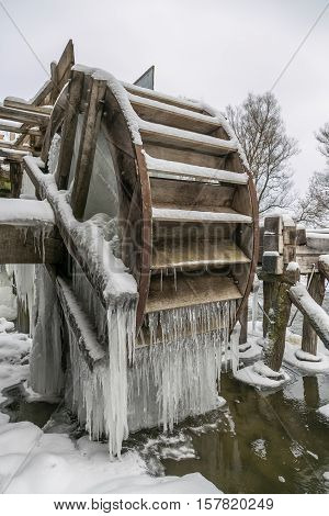 Wheel of Old watermill covered with icicles in Krasnikovo, Kursk region