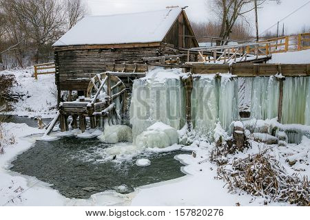Old watermill in Krasnikovo, Kursk region. Winter, watermill is frozen in ice, covered with IciclesOld watermill in Krasnikovo, Kursk region. Winter, watermill is frozen in ice, covered with Icicles