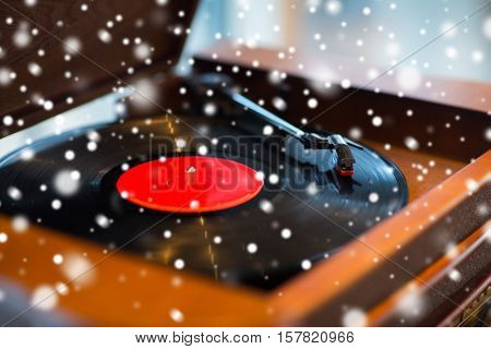 music, technology and object concept - close up of vintage record player with vinyl disc over snow