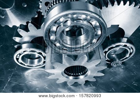 cogwheels, gears and ball-bearings in steel-blue toning concept
