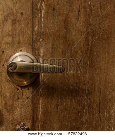 Golden doorknob on wooden door closed up