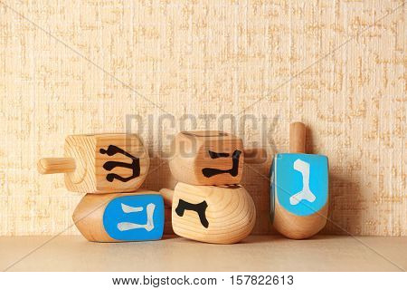 Dreidels for Hanukkah on light table against textured wall