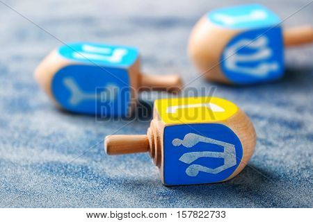Wooden dreidel for Hanukkah on light sparkling background, close up