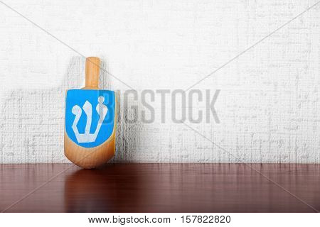 Dreidel for Hanukkah on wooden table against light textured wall