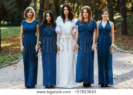 Bride with bridesmaid standing straight in the park