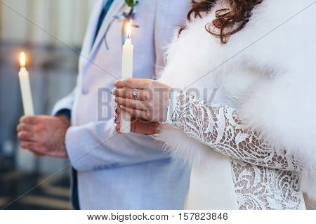 Fiance and bride holding candles during the ceremony