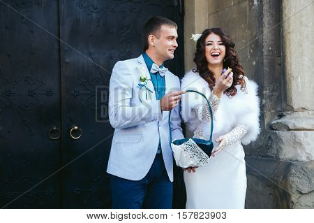 Bride and fiance holding sweets for guests